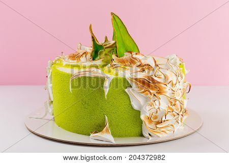 Green Cake Decorated With Burned Meringue And Colored Pear Slices