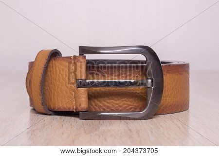 men's leather belt with a buckle on a wooden board