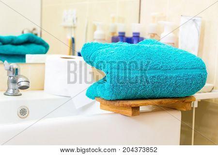 Blue towels on bathtub in white bathroom.