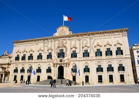 VALLETTA, MALTA - MARCH 30, 2017 - View of the Auberge de Castille in Castille Square with tourists enjoying the setting Valletta Malta Europe, March 30, 2017.