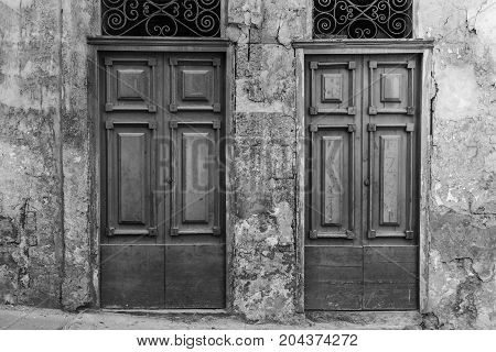 Building with traditional maltese doors in historical part of Valletta. Entrance to an abandoned house on the island of Malta. Black and white picture