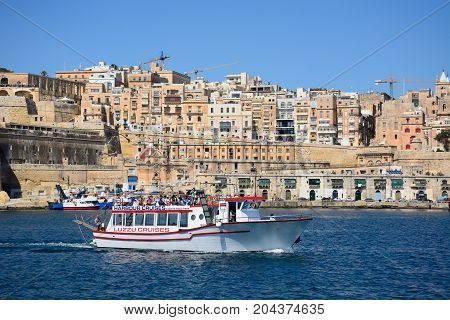 VALLETTA, MALTA - MARCH 31, 2017 - View across the Grand Harbour towards Valletta city seen from Vittoriosa with a tour boat in the foreground Valletta Malta Europe, March 31, 2017.