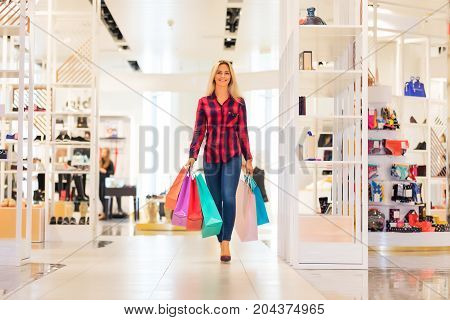 Young blonde smiling attractive woman with long hair with a lot of color shopping bags walks in the fashion wear garments apparel store