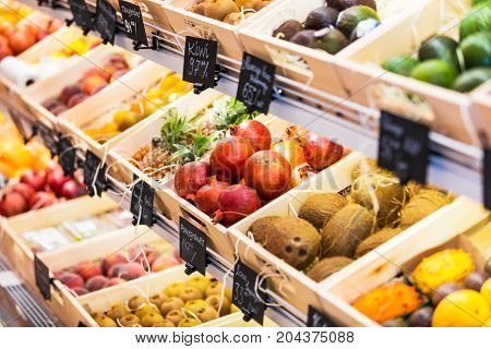 Assortment of fresh exotic fruits in the grocery store - pineapples, coconuts, avocado, kiwi, oranges and other