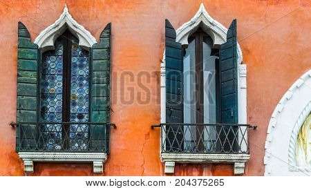 Ogival mosaic Venetian windows with shutter. Houses peeling off from dampness in Venice