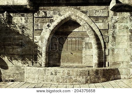 Aged Drinking Fountain in old Acre in Israel. Arab architecture of the old city of Akko. Vintage style toned picture