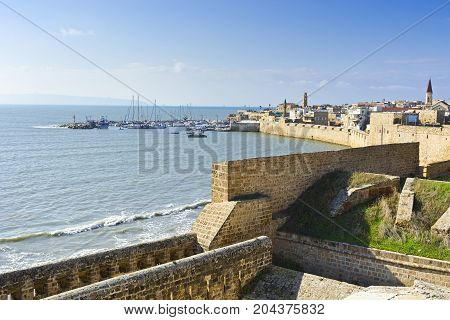 Embankment and city beach of old arabic city Akko located north of Israel. Sailboats moored at the marina in Acre