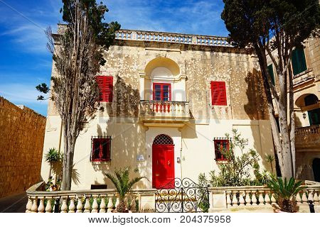 MDINA, MALTA - APRIL 1, 2017 - Townhouse with a red door and window frames in Bastion Square Mdina Malta Europe, April 1, 2017.