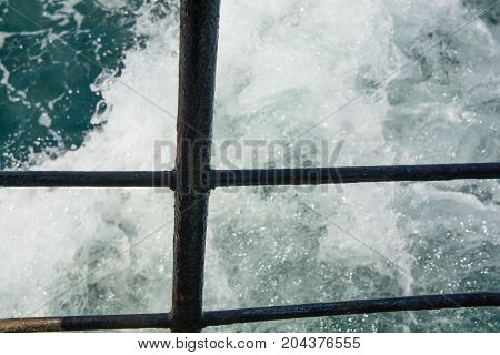 Sea track behind the ship railing. Water foaming in motion.