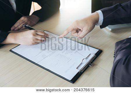 Closeup of woman applicant writing in resume form person completing filling information and executive pointing help her to sign in application form hiring concept.