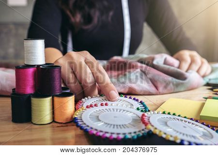 Young woman dressmaker or designer working as fashion designers Select the needle to the sewing fabric profession and job occupation.