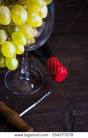 Bottle of wine and wine glass full of ripe grapes on dark wooden table