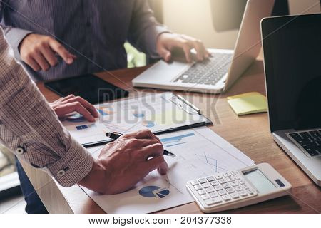 Teamwork process Business team two managers colleagues discussing and analysis new plan financial graph data and marketing documents report on office table with laptop and digital tablet.