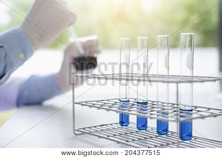 Scientist or medical in lab coat working in biotechnological laboratory equipment holding test tube for research with mixing reagents in glass flask in laboratory.