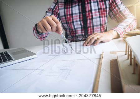 Architect working on blueprint Engineer working with engineering tools for architectural project on workplace.
