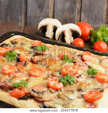 Homemade pizza with tomatoes mushrooms sausage and cheese over wooden background selective focus square shot