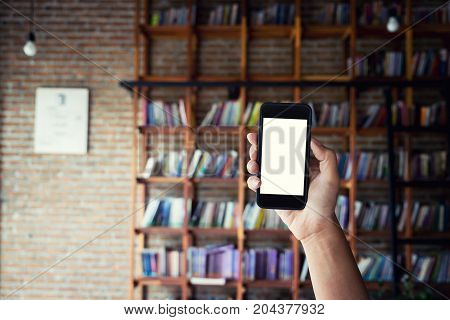 Man holding blank screen of a smartphone at the library.