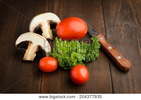 Tomatoes mushrooms and parsley with knife over brown wooden background