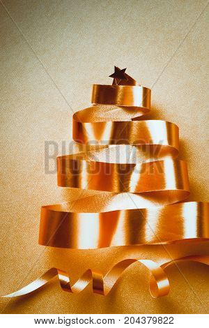 Christmas tree from gold tapes on yellow background.