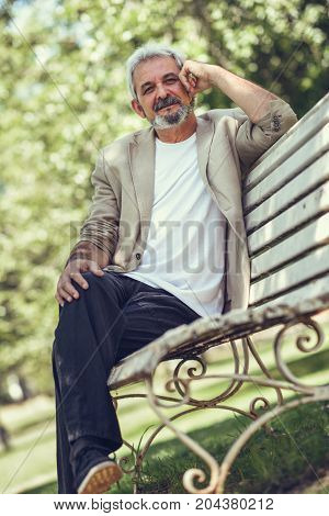 Pensive Mature Man Sitting On Bench In An Urban Park.