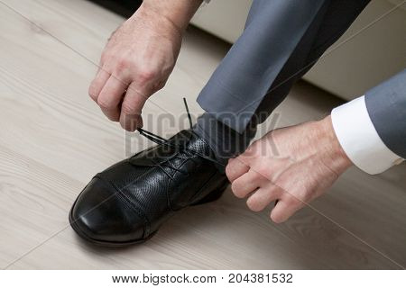 businessman in gray suit and white shirt tie shoelaces