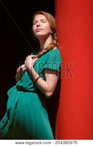 Young Pretty Woman In Green Dress Basking In The Sun With Closed Eyes, Copy Space