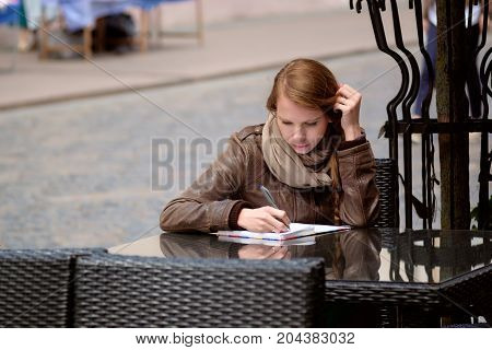 Redhead Girl Sitting In Town Street Cafe And Writing Or Drawing In Scetchbook