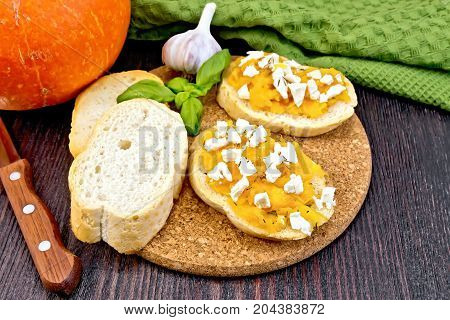 Bruschetta with pumpkin, salted feta cheese, garlic and basil, green napkin, knife and orange vegetable on a wooden board background