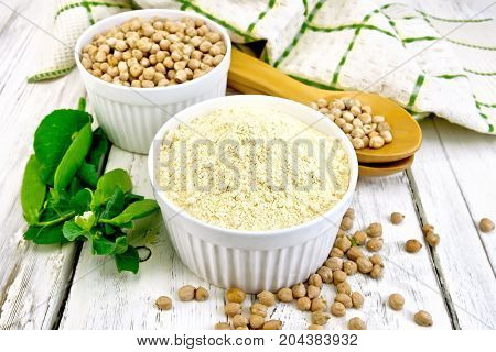 Flour chickpeas and chick-pea in white bowls and spoons, pods of green beans, a towel on the background light wooden boards