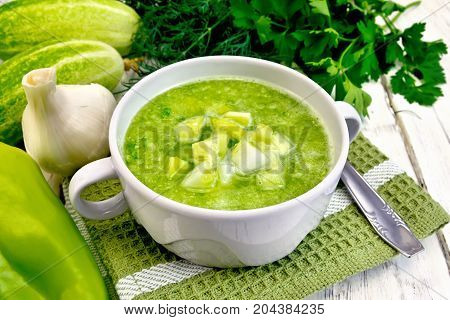 Cucumber soup with green peppers and garlic in a bowl on green napkin, parsley on a wooden boards background
