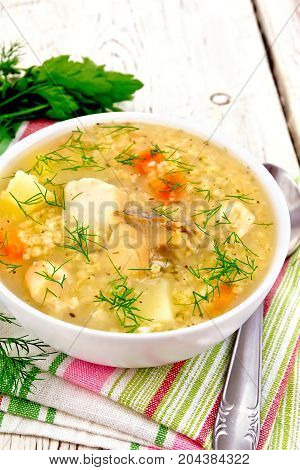 Soup fish kulesh with millet, potatoes and carrots in a bowl on a napkin, parsley, dill on a wooden plank background