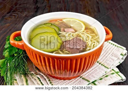 Soup with zucchini, beef, ham, lemon and noodles in a red bowl, parsley and dill on a napkin on a background of a dark wooden board