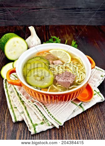 Soup with zucchini, beef, ham, lemon and noodles in a bowl, parsley and dill on a napkin on a wooden board background