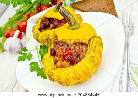 Two yellow squash stuffed with meat, tomatoes and peppers in the dish, bread, garlic, parsley and a napkin on the background light wooden boards