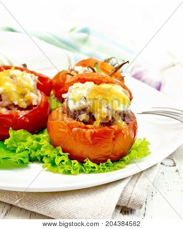 Tomatoes stuffed with meat and rice with cheese on lettuce in a plate on a napkin, fork against a light wooden board