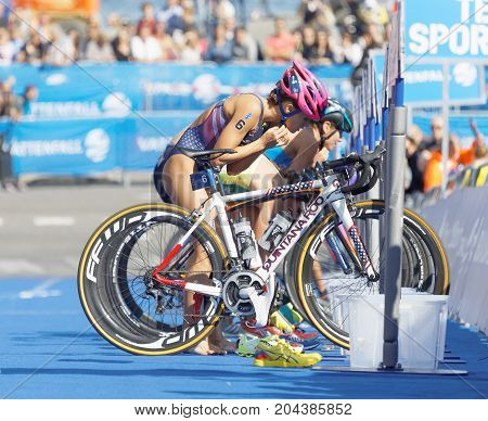 STOCKHOLM - AUG 26 2017: Female triathletes Taylor Spivey (USA) and competitors taking of helmets in the transition zone in the Women's ITU World Triathlon series event August 26 2017 in Stockholm Sweden