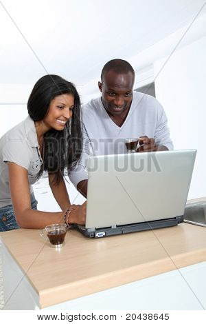 Young couple with laptop computer in home kitchen