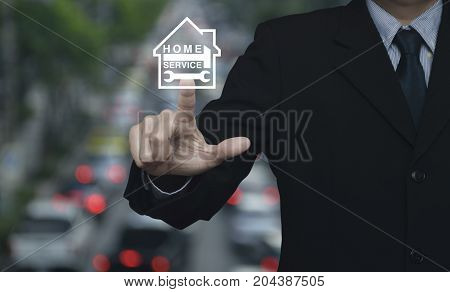 Businessman pressing hammer and wrench with house icon over blur of rush hour with cars and road Home service concept