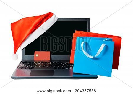 Opened laptop with red santa claus hat put on display corner credit card and shopping bags isolated on white background. Christmas online shopping concept.