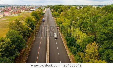 Vinnytsia Ukraine - August 24 2017: Top view of asphalt road passes through the field and forest.