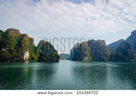 Beautiful view of lagoon in the Halong Bay (Descending Dragon Bay) at the Gulf of Tonkin of the South China Sea Vietnam. Landscape formed by karst towers-isles on blue sky background.