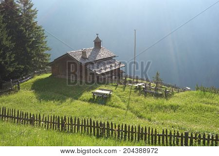 An Alpine meadow with old wooden farmhouse, Dolomites, Italian Alps in summer sunrise light