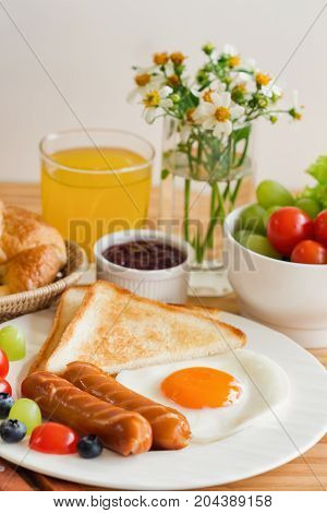Homemade breakfast with sunny side up fried egg toast sausage fruits vegetable strawberry jam and orange juice in side view. Delicious homemade american breakfast concept for background or wallpaper. American breakfast on breakfast table.