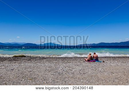 Two people tourists are laying down to sunbathe on sandy coastline.