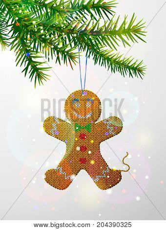 Christmas tree branch with knitted gingerbread man. Christmas ornament of knitted fabric hanging on pine twig