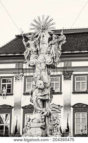 Holy trinity column and Goose on a string theatre building Brno Moravia Czech republic. Baroque architecture. Black and white photo.