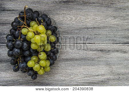 Pictures of black grapes on a wooden floor, black and green grapes pictures in the plate, the great black grapes