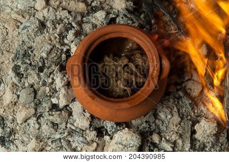 a dish in a clay pot is prepared on burning coals. the dish is cooked and smoked on charcoal