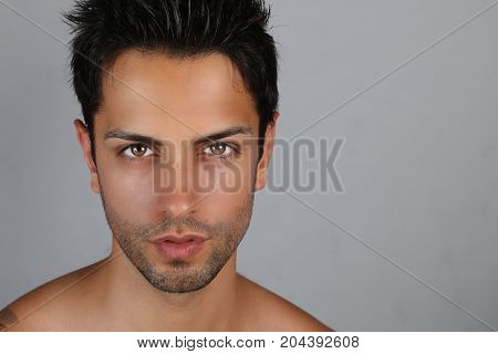 Portrait of handsome man shirtless on a gray background