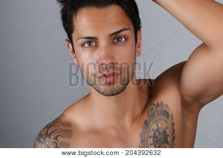 sexy male model posing shirtless on a gray background